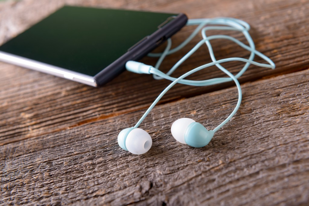 bigstock-Small-headphones-with-mobile-p-73482259-1024x683